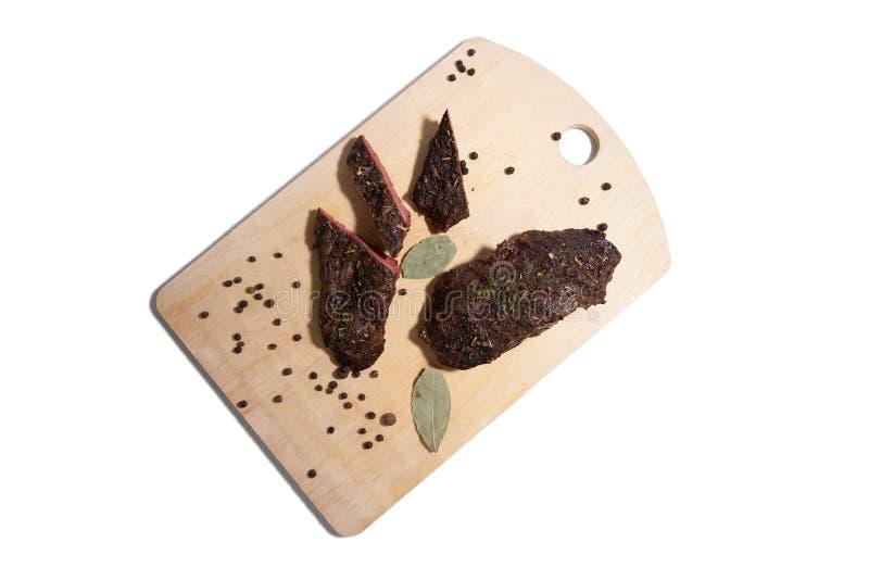 Il pezzo di arrosto di manzo con le spezie ? servito sul tagliere di legno fotografie stock libere da diritti