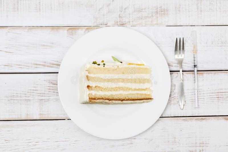 Il pezzo di dolce è servito sulla coltelleria del piatto e sulla siringa dell'insulina accanto  fotografie stock libere da diritti