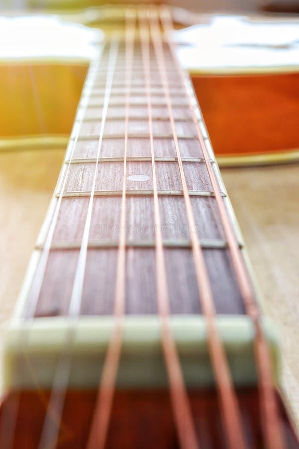 Il phto d'annata delle corde della chitarra acustica sulla tavola di legno nella stanza, la fine sulla vista superiore e la luce  fotografia stock