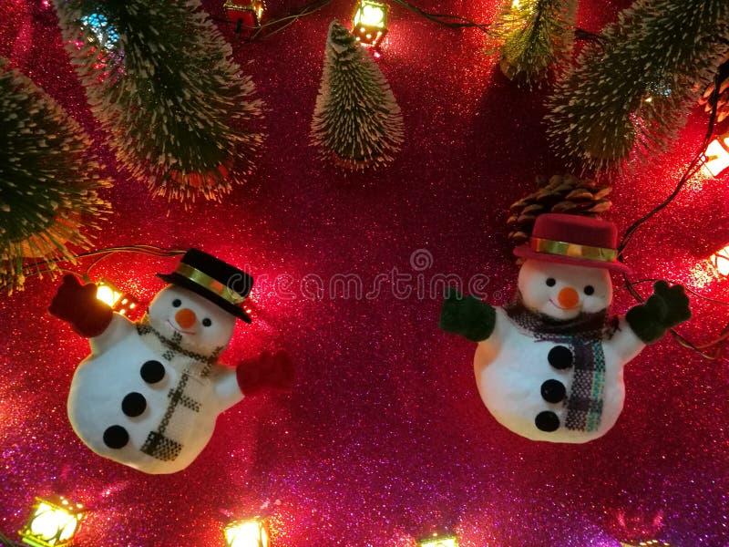 Il piano adorabile del pupazzo di neve mette sul fondo rosa del gliter vicino alla lampadina dell'ornamento alla notte silenziosa immagini stock libere da diritti