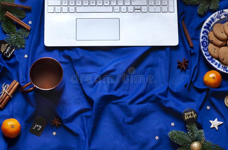 Il piano blu del nuovo anno di Natale mette sulla coperta del letto con la tastiera del computer portatile Carta festiva di vacan fotografia stock libera da diritti