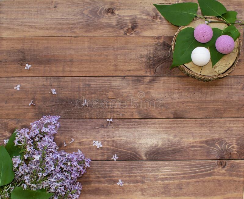 Il piano cosmetico pone con un lillà dei fiori del mazzo Bombe infuriantesi fatte a mano della stazione termale sulla fetta di le fotografie stock