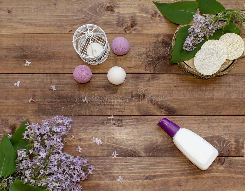 Il piano cosmetico pone con un lillà dei fiori del mazzo Insieme della stazione termale della crema della bottiglia, bombe fatte  immagine stock libera da diritti