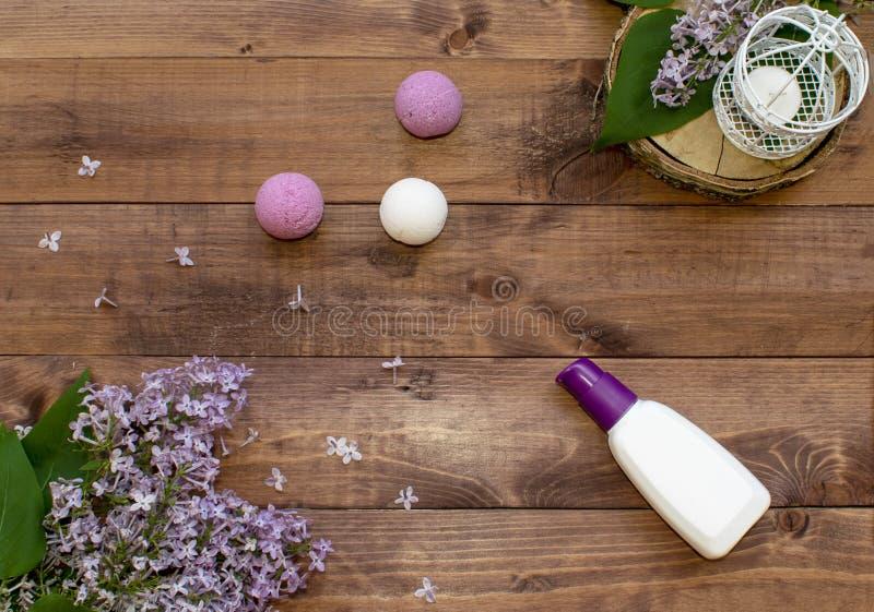 Il piano cosmetico pone con un lillà dei fiori del mazzo Insieme della stazione termale della crema della bottiglia, delle bombe  fotografie stock