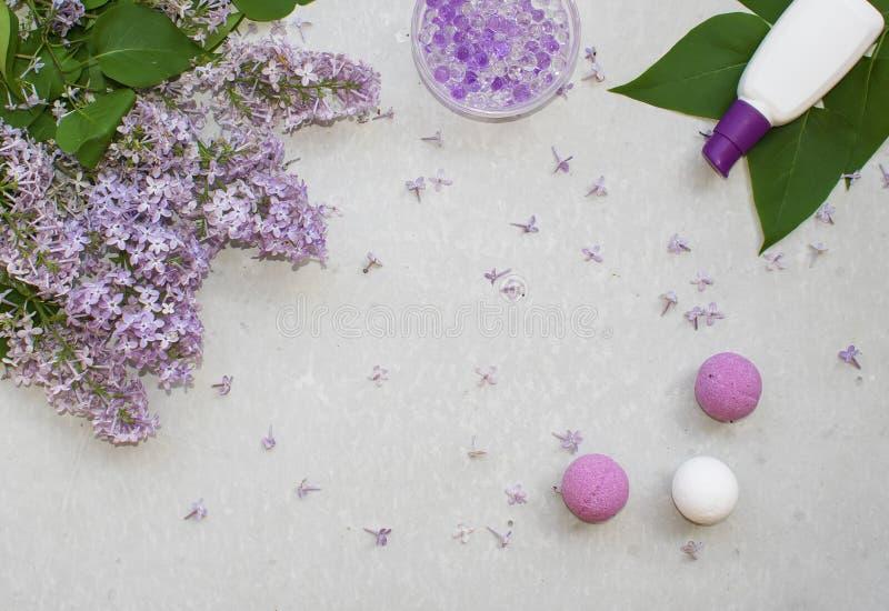 Il piano cosmetico pone con un lillà dei fiori del mazzo Insieme della stazione termale delle bombe infuriantesi fatte a mano, de fotografie stock