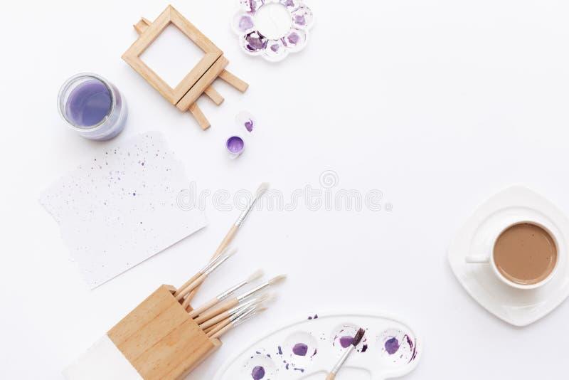 Il piano creativo pone l'area di lavoro di arte con le tavolozze gialle, pennelli, fotografia stock