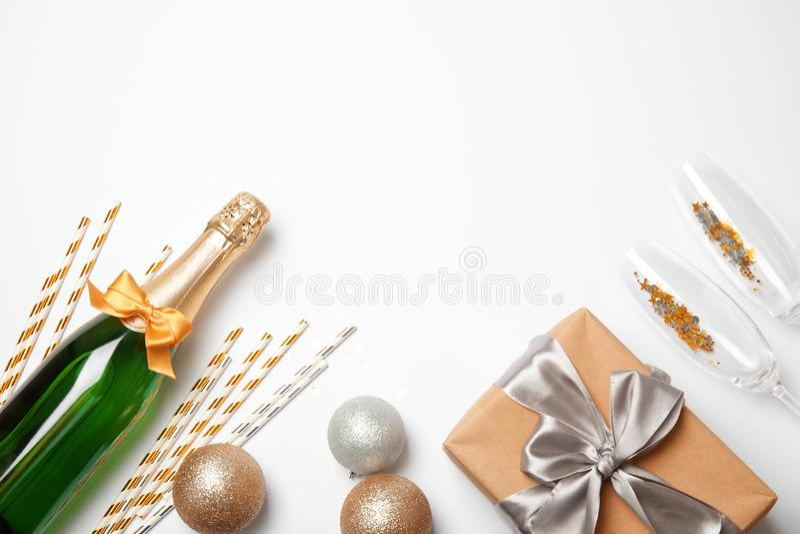 Il piano creativo pone la composizione con la bottiglia di champagne e fa festa gli accessori su fondo bianco immagine stock