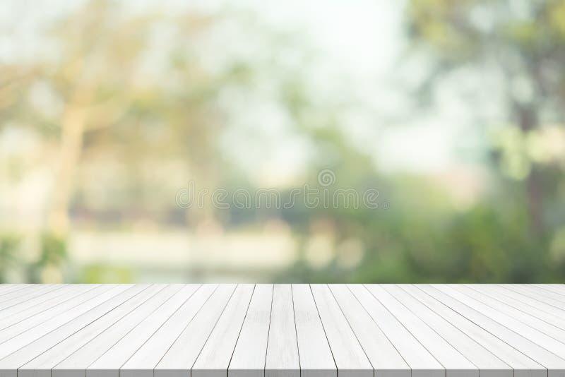 Il piano d'appoggio di legno bianco su verde ha offuscato il fondo, spazio per il monta immagini stock