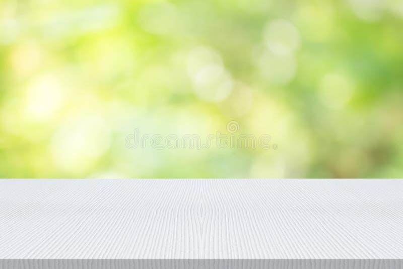 Il piano d'appoggio di legno bianco vuoto su verde della natura ha offuscato il fondo, PS immagine stock