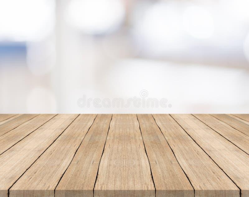 Il piano d'appoggio di legno vuoto su bianco ha offuscato il fondo immagine stock libera da diritti