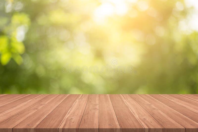 Il piano d'appoggio di legno vuoto su verde della natura ha offuscato il fondo a garde immagine stock libera da diritti