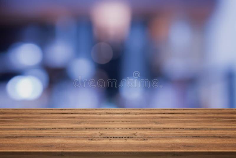 Il piano d'appoggio di legno vuoto sul blu astratto ha offuscato il fondo, per lunedì immagini stock