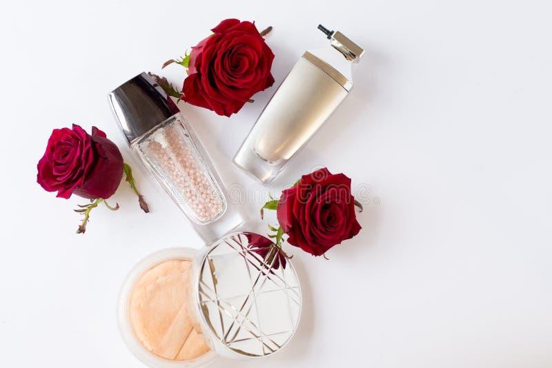 Il piano decorativo pone la composizione con i cosmetici ed i fiori Disposizione piana, vista superiore su fondo bianco con lo sp fotografia stock libera da diritti
