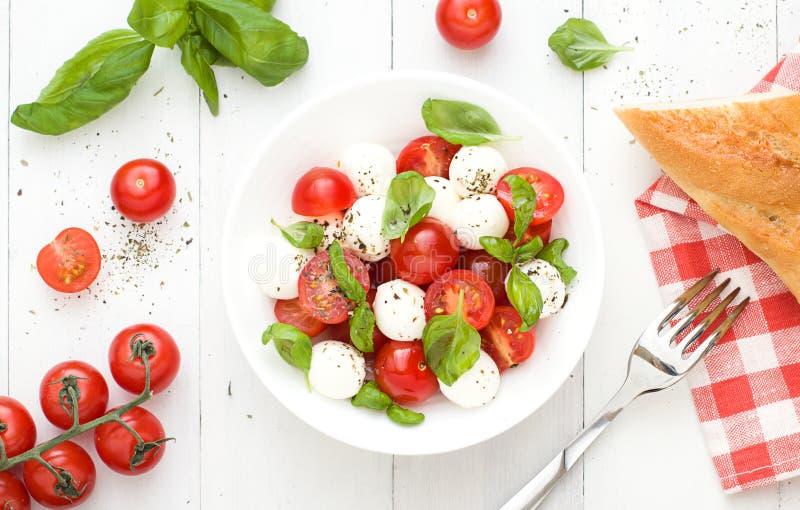 Il piano dell'insalata di Caprese mette sui precedenti bianchi Vista superiore immagini stock