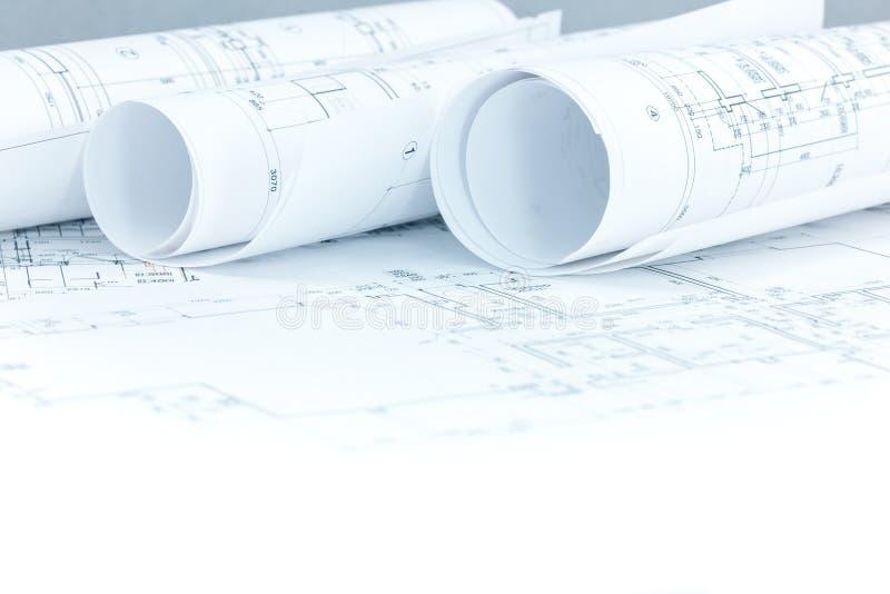 Il piano della costruzione in corso ed il modello rotola sull'architetto w immagini stock libere da diritti