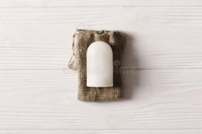 Il piano di cristallo naturale del deodorante dell'allumite di Eco mette sul backgro rustico immagini stock