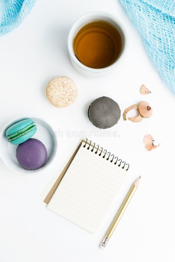 Il piano di vista superiore pone il modello del taccuino allineato spazio in bianco con i macarons e la tazza di tè su bianco Art fotografie stock