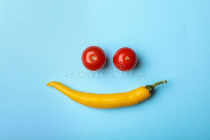 Il piano divertente pone la composizione con i pomodori ciliegia ed il peperoncino fotografia stock