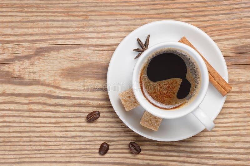 Il piattino e la tazza di caffè bianchi hanno decorato le spezie, lo zucchero di canna ed i chicchi di caffè sulla tavola di legn fotografia stock