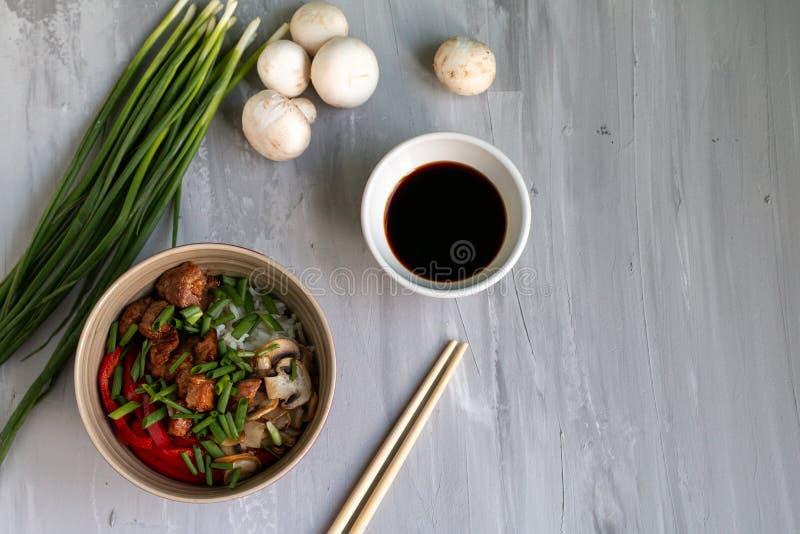 Il piatto asiatico tradizionale con l'aumento ed il wok ha arrostito la carne, le verdure ed i funghi Vista superiore con spazio  fotografia stock libera da diritti