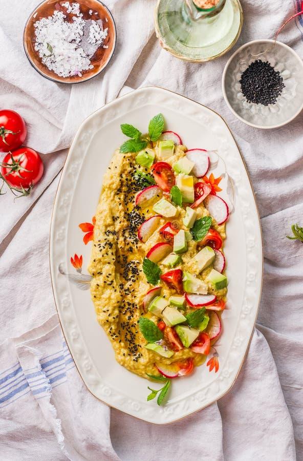 Il piatto casalingo di hummus ha completato con olio d'oliva, l'avocado, gli ortaggi freschi e le erbe sul tavolo da cucina, vist fotografia stock libera da diritti