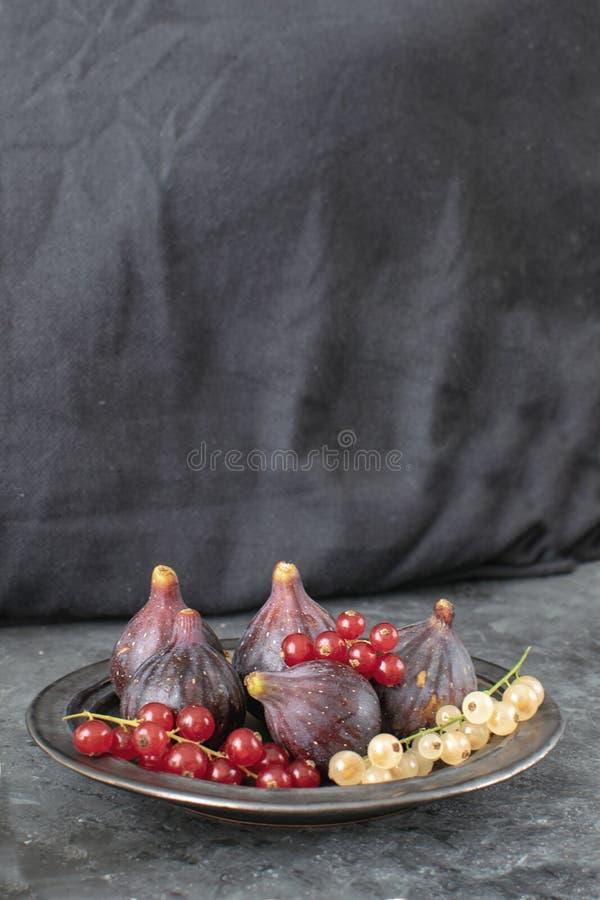 Il piatto ceramico dei fichi organici maturi ha isolato il backgr nero del fondo fotografia stock libera da diritti