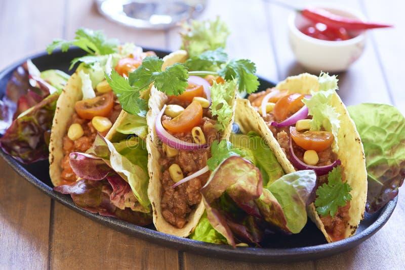 Il piatto con il taco, l'insalata ed il pomodoro immergono fotografia stock libera da diritti
