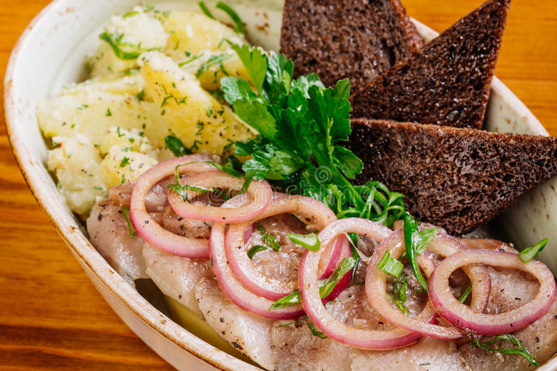 Il piatto con l'aringa, le patate, le cipolle ed i bastoni di Bried immagini stock