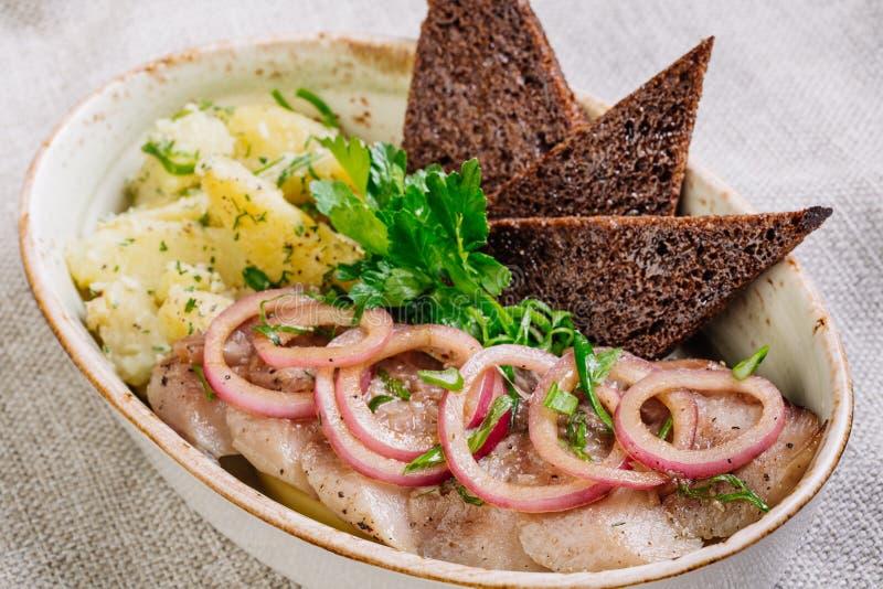Il piatto con l'aringa, le patate, le cipolle ed i bastoni di Bried fotografia stock libera da diritti