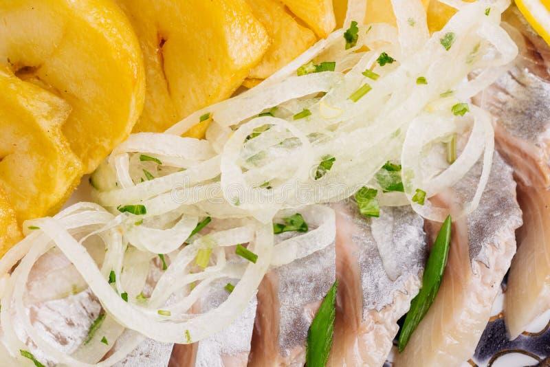Il piatto con l'aringa, le patate, le cipolle ed i bastoni di Bried fotografie stock libere da diritti