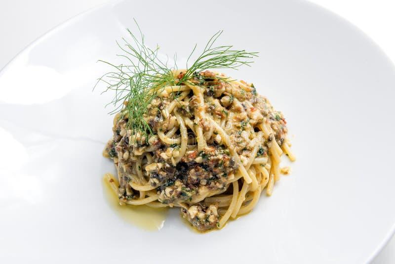 Il piatto degli spaghetti con salsa dei pinoli delle olive dei capperi si è asciugato a fotografia stock libera da diritti