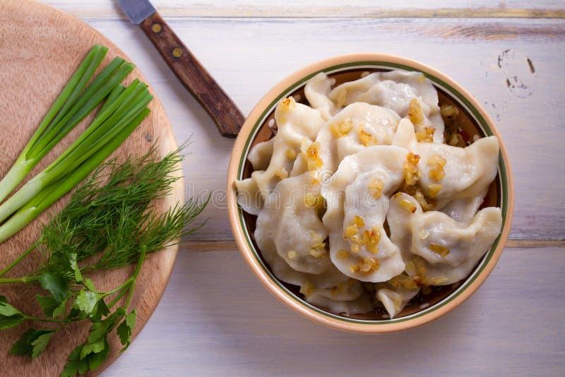 Il piatto del pierogi o varenyky, vareniki, gnocchi, ha riempito di carne del manzo ed è servito con la cipolla fritta fotografia stock