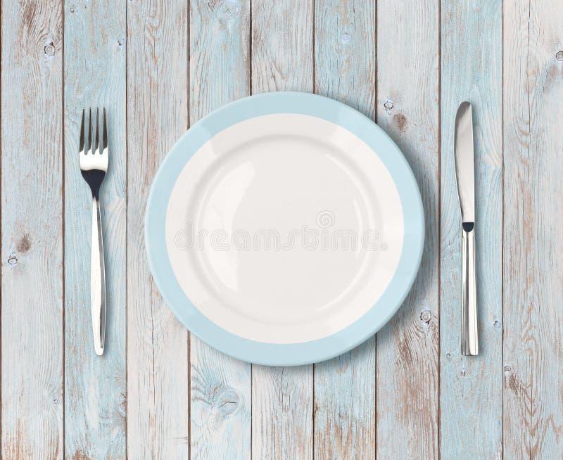Il piatto di cena vuoto bianco con il blu rasenta la tavola di legno fotografie stock