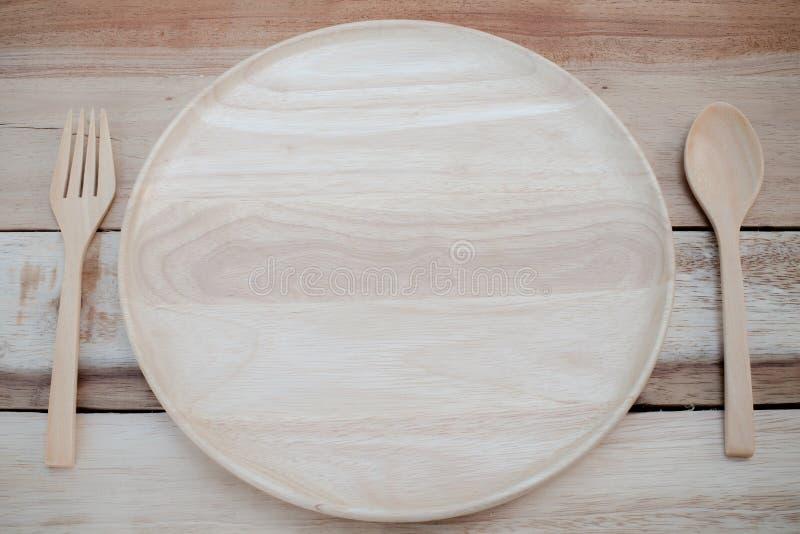 Il piatto ed il legno di legno si biforcano su colore di legno dell'annata e della tavola fotografia stock