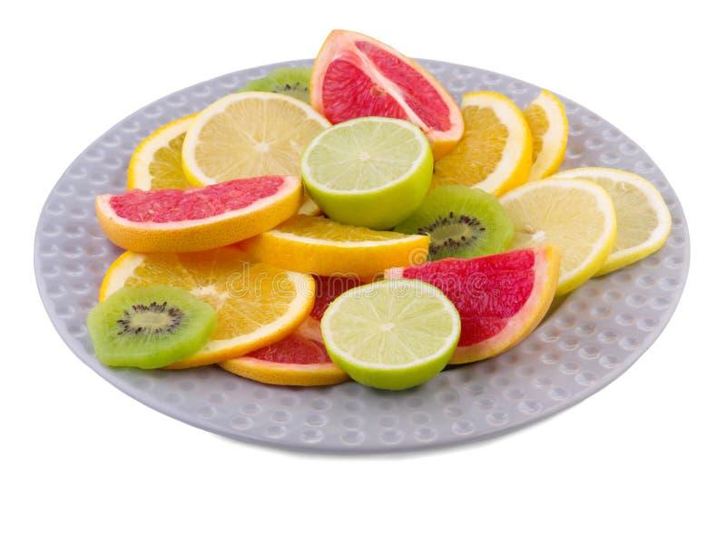 Il piatto pieno dei frutti tropicali ha affettato il primo piano su fondo isolato bianco immagini stock libere da diritti