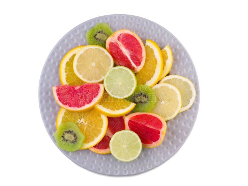 Il piatto pieno dei frutti tropicali ha affettato il primo piano su fondo isolato bianco Vista da sopra fotografia stock libera da diritti