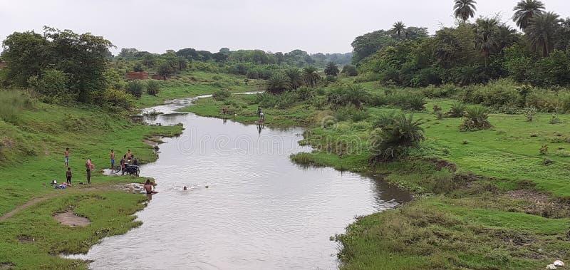 Il piccoli fiume e gente indiani stanno bagnando immagine stock