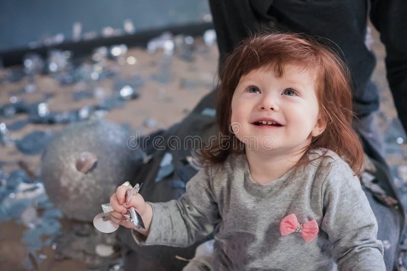 Il piccolo bambino ammira al Natale i coriandoli e un abete fotografia stock libera da diritti