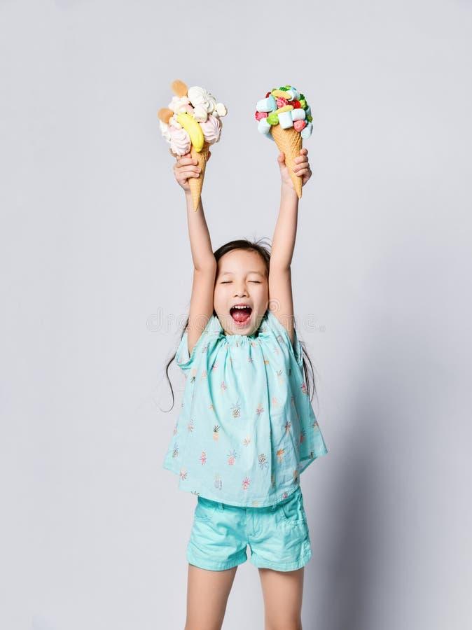 Il piccolo bambino asiatico della ragazza con gli occhi chiusi con felicità sostiene il grande gelato dolce su due nei coni delle fotografia stock