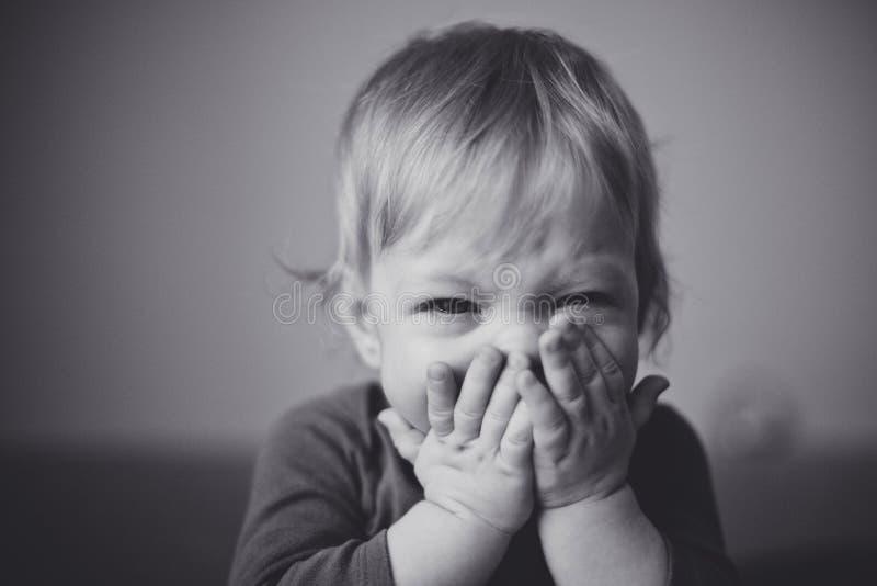 Il piccolo bambino biondo sveglio è amaramente grida e stampe le sue mani al suo fronte Fine in su fotografie stock libere da diritti