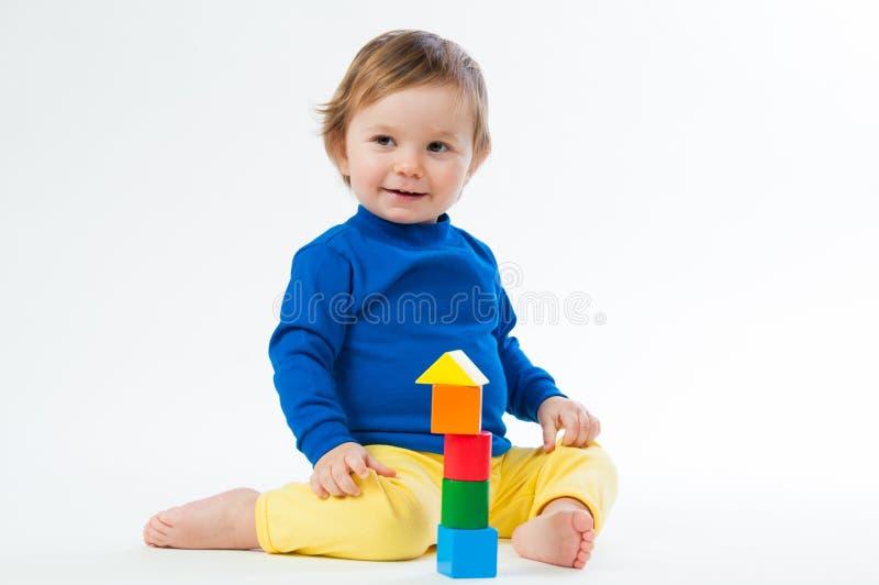 Il piccolo bambino che gioca con taglia isolato su fondo bianco fotografia stock