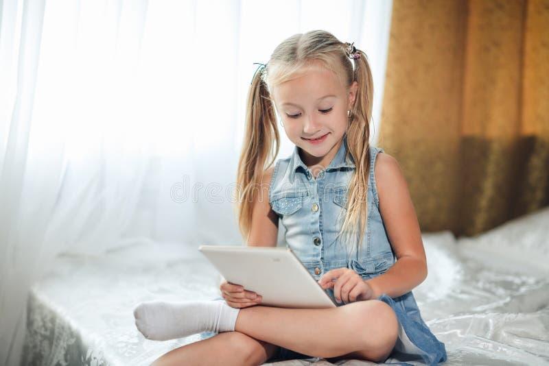 Il piccolo bambino che sveglio la ragazza bionda in prendisole del denim si trova a letto utilizza la compressa digitale bambino  immagine stock