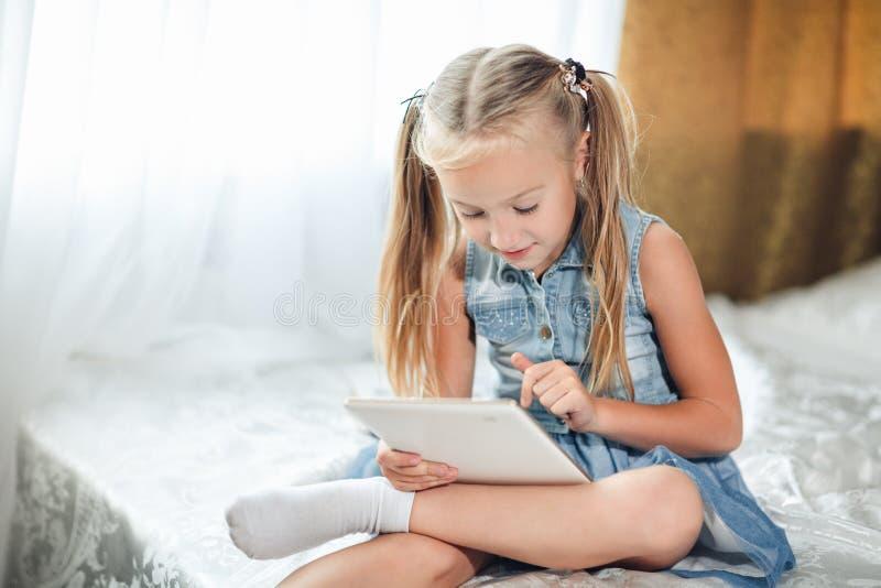 Il piccolo bambino che sveglio la ragazza bionda in prendisole del denim si trova a letto utilizza la compressa digitale Bambino  fotografia stock libera da diritti