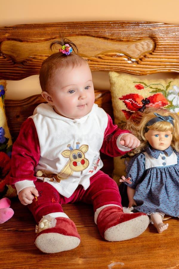 Il piccolo bambino con una coda si siede su un sofà con i cuscini ed i giocattoli ricamati fotografia stock libera da diritti