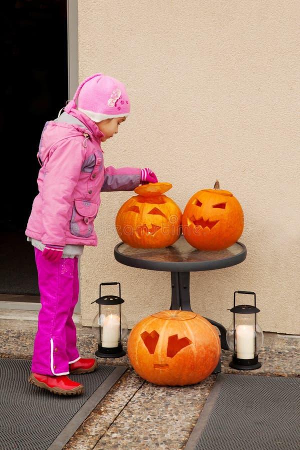 Il piccolo bambino considera la zucca di Halloween. fotografie stock