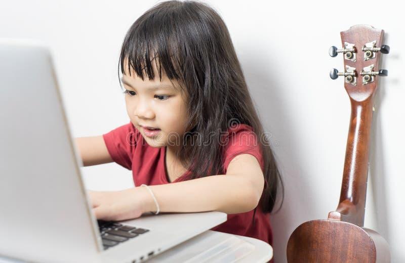 Il piccolo bambino del musicista sta lavorando alla sua musica su un computer portatile fotografie stock libere da diritti