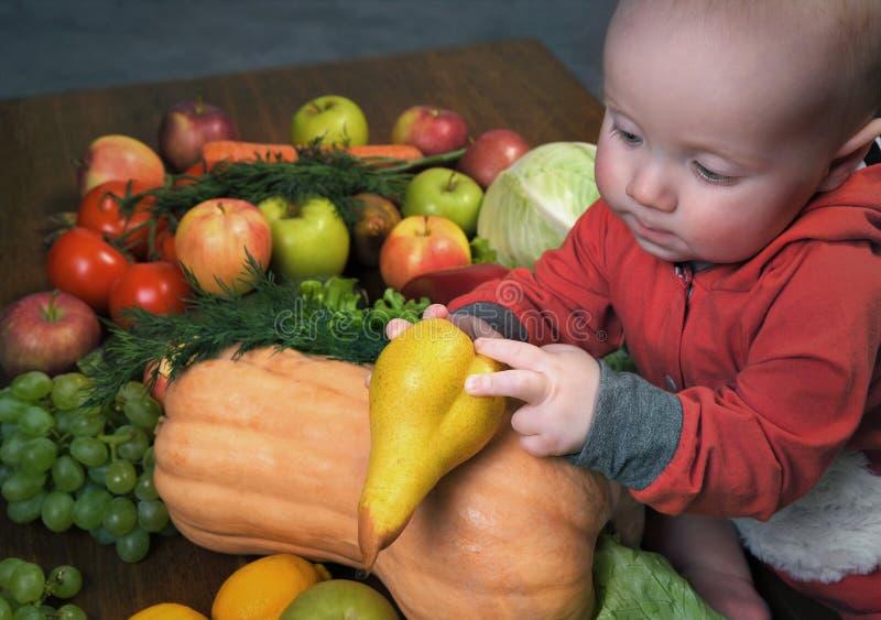 Il piccolo bambino esamina una verdura della pera fra le varie verdure fotografie stock libere da diritti