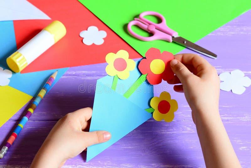 Il piccolo bambino fa i mestieri di carta per il giorno o il compleanno del ` s della madre Piccolo bambino che fa i fiori di car immagine stock