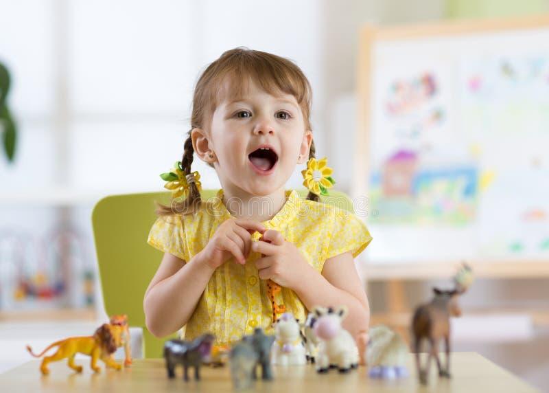 Il piccolo bambino felice gioca i giocattoli animali a casa o il centro di guardia fotografia stock