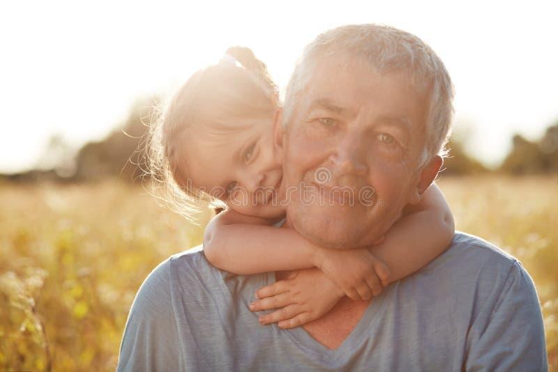 Il piccolo bambino femminile sveglio con il sorriso delicato abbraccia suo nonno, ha espressioni allegre, gode dell'unità e del g immagini stock